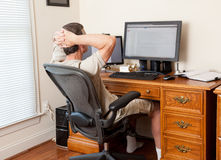 Senior male working in home office. Senior caucasian man working from home in shorts with desk with two monitors Royalty Free Stock Photo