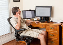 Senior male working in home office. Senior caucasian man working from home in shorts with desk with two monitors Stock Photo