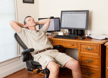 Senior male working in home office. Senior caucasian man working from home in shorts with desk with two monitors Stock Image