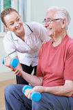 Senior Male Working With Physiotherapist Using Weights. Senior Male Working With Female Physiotherapist Using Weights Royalty Free Stock Image