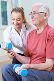 Senior Male Working With Physiotherapist Using Weights. Senior Male Works With Physiotherapist Using Weights Royalty Free Stock Images