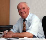 Senior man. In a shirt with short sleeves sitting in the office Stock Photos