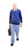Senior man. Portrait of a happy senior carrying a suitcase on white background Royalty Free Stock Images