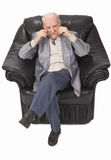 Senior man. Sitting in an armchair and putting on his glasses Stock Image
