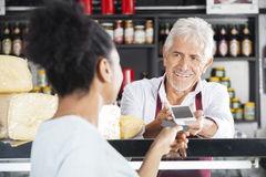 Senior Man Accepting Payment From Customer In Cheese Shop Stock Images