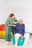 Senior man with aching back in physical therapy Stock Photography