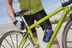Senior Man Adjusting Bicycle Seat. Mid section of senior man adjusting bicycle seat Royalty Free Stock Images