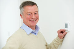 Senior Man Adjusting Central Heating Thermostat. Senior Man Adjusts Central Heating Thermostat Royalty Free Stock Images