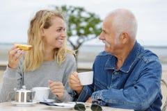 Senior man with adult daughter having breakfast royalty free stock image