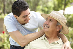 Senior Man With Adult Son In Garden Royalty Free Stock Images