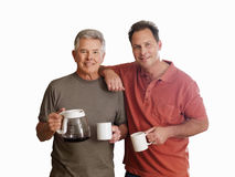Senior man and adult son holding mugs and coffeemaker, smiling, portrait, cut out Stock Photos