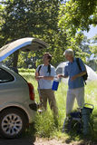 Senior man and adult son unloading parked car on camping trip in woodland clearing, side view. Senior men and adult son unloading parked car on camping trip in Stock Photo