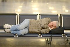 Senior man in airport. Sleeping on a bench Royalty Free Stock Photography
