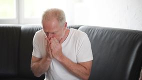 Senior man with allergy sneezing and blowing his nose stock footage