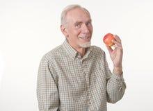 Senior man with apple. Studio shot of smiling senior man with healthy apple Stock Photo