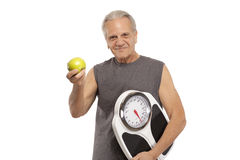 Senior man with apple and weight scale Royalty Free Stock Photos