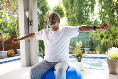 Senior man with arms outstretched lifting dumbbell while exercising Stock Photo