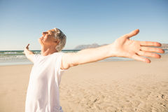 Senior man with arms outstretched standing at beach Stock Image