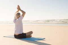 Senior man with arms raised meditating at beach Royalty Free Stock Images