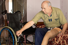 Senior man with an artificial leg and wheelchair Stock Photo