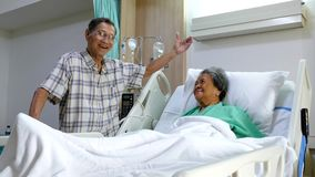 Senior man as he visits wife in hospital room. Senior man as he visits wife being sick in hospital room stock video footage