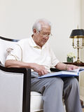 Senior man. Senior asian man sitting in an armchair and reading Stock Images