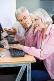 Senior Man Asking Questions To Bored Classmate In Computer Class Stock Photography