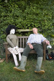 Senior man asleep on bench by scarecrow Royalty Free Stock Image