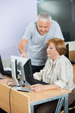 Senior Man Assisting Friend In Computer Class Stock Images