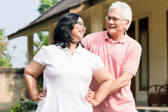 Senior man assisting his wife during warming up exercises outdoo Royalty Free Stock Photo