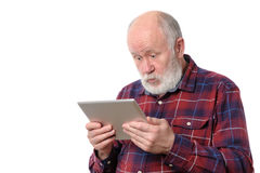 Senior man astonished with something at screen of tablet computer, isolated on white. Senior bald and bearded white haired man astonished with something at Stock Images