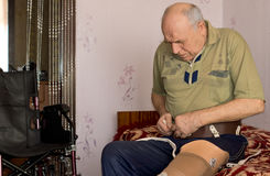 Senior man attaching his artificial leg at home. Elderly man attaching the electronics to control his artificial leg following an above the knee amputation Royalty Free Stock Photography