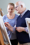 Senior Man Attending Painting Class With Teacher. Senior Man Attends Painting Class With Teacher stock photo