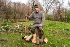 Senior man with ax in the autumn garden. Senior man sitting on the tree trunk to rest after split wood with ax Royalty Free Stock Images