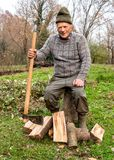 Senior man with ax in the autumn garden. Senior man sitting on the tree trunk to rest after split wood with ax Stock Photography