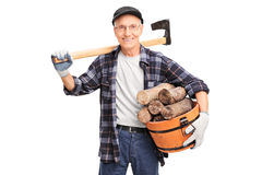 Senior man with an axe holding basket full of logs Stock Photography