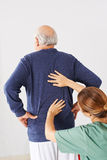 Senior man with back pain in physical therapy. Physiotherapist laying hands on senior men with back pain in physical therapy Royalty Free Stock Images