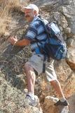 Senior man climbing on rock stock image