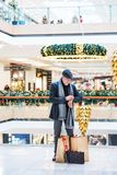 Senior man with bags standing in a shopping center at Christmas time, checking the time. A senior man with bags standing in a shopping center at Christmas time stock photo