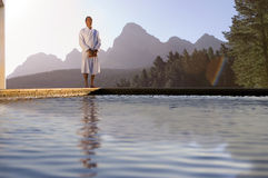 Senior man in bathrobe on edge of swimming pool, low angle view (lens flare) Royalty Free Stock Photography