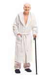 Senior man in a bathrobe holding a cane Royalty Free Stock Photo