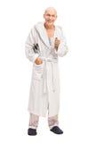 Senior man in a bathrobe holding a newspaper Royalty Free Stock Image