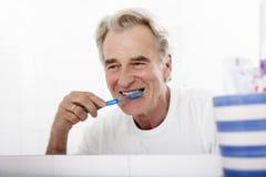 Senior Man In Bathroom Brushing Teeth Royalty Free Stock Photo