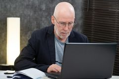 Senior man with beard and blue shirt in the office using laptop royalty free stock image