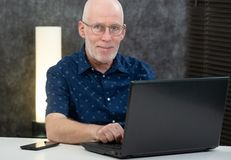 Senior man with beard and blue shirt in the office using laptop stock image
