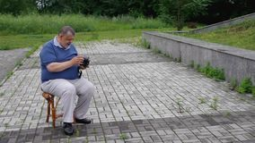Senior man becomes irritable when realize he forgotten to install film roll to an old medium format film camera. Senior man becomes irritable when realize he stock video footage