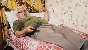 Senior man in the bed at home with TV remote control.  stock footage