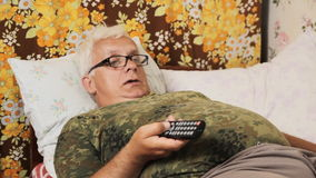 Senior man in the bed at home with TV remote control.  stock video footage