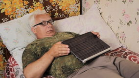 Senior man in the bed at home with TV remote control.He does not like TV, and he takes the laptop.  stock footage