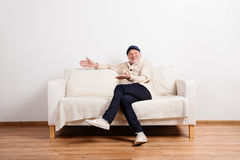 Senior man in beige sweater sitting on sofa, studio shot. Royalty Free Stock Photos